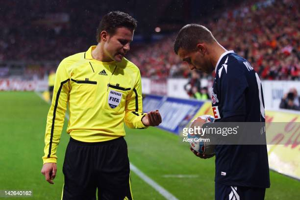 Lukas Podolski of Koeln listens to referee Felix Brych reacts after being hit by a coin during the Bundesliga match between between FSV Mainz 05 and...