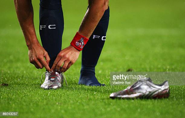 Lukas Podolski of Koeln takes off his shoes after the preseason friendly match between 1 FC Koeln and FC Bayern Muenchen at RheinEnergie Stadium on...