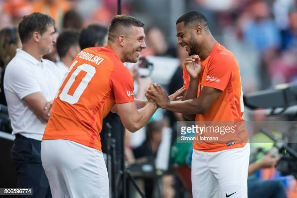 Lukas Podolski of Nowitzki All Stars jokes with Serge Gnabry during the Champions for Charity Friendly match at Opel Arena on July 3 2017 in Mainz...
