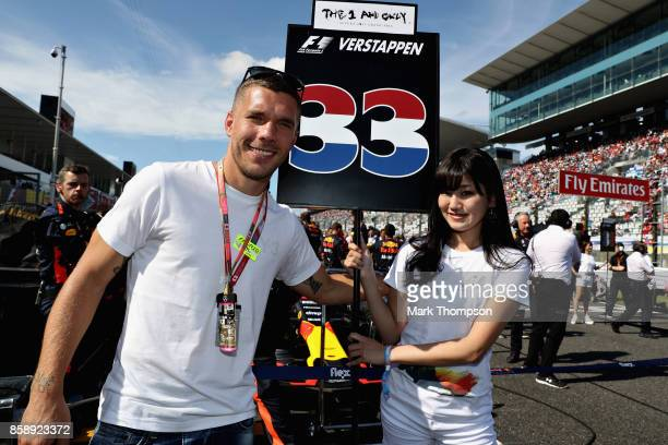 Lukas Podolski of Vissel Kobe and Germany poses for a photo with the car of Max Verstappen of Netherlands and Red Bull Racing on the grid before the...