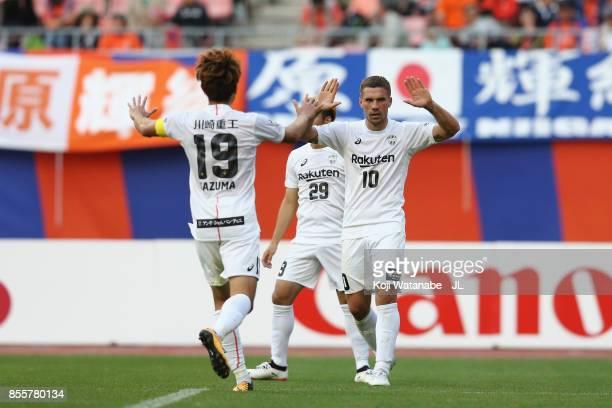 Lukas Podolski of Vissel Kobe celebrates scoring his side's second goal with his team mates Kazuma Watanabe and Kotaro Omori during the JLeague J1...