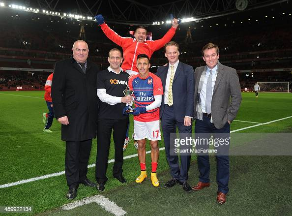 Lukas Podolski photobombs the Alexis Sanchez PFA Fans Player Of The Month presentation before the Barclays Premier League match between Arsenal and...