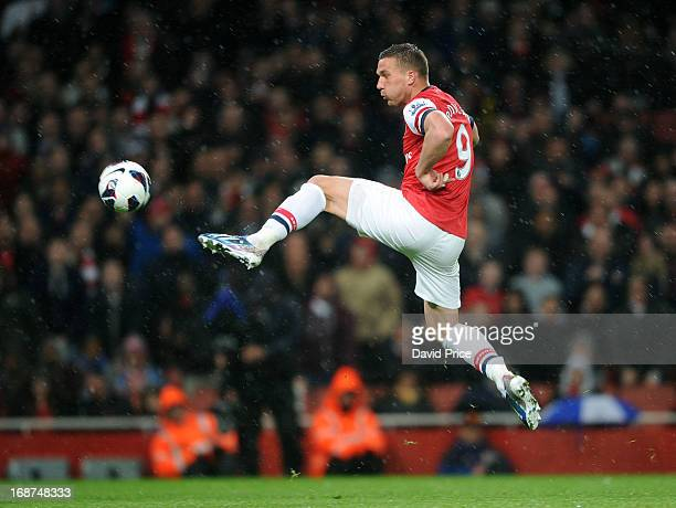Lukas Podolski scores Arsenal's 3rd goal during the Barclays Premier League match between Arsenal and Everton at Emirates Stadium on April 16 2013 in...