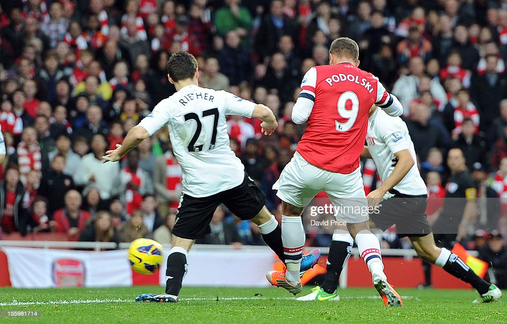 <a gi-track='captionPersonalityLinkClicked' href=/galleries/search?phrase=Lukas+Podolski&family=editorial&specificpeople=204460 ng-click='$event.stopPropagation()'>Lukas Podolski</a> scores Arsenal's second goal under pressure from <a gi-track='captionPersonalityLinkClicked' href=/galleries/search?phrase=Sascha+Riether&family=editorial&specificpeople=614139 ng-click='$event.stopPropagation()'>Sascha Riether</a> of Fulham during the Barclays Premier League match between Arsenal and Fulham, at Emirates Stadium on November 10, 2012 in London, England.