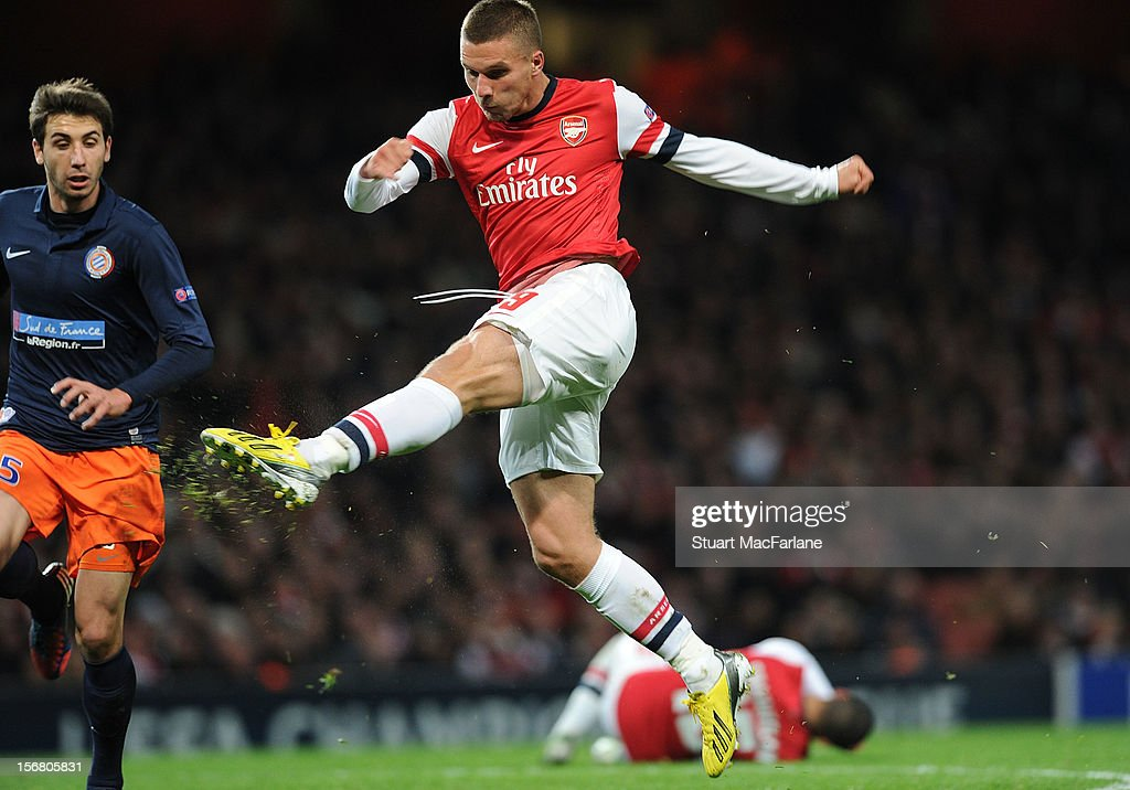 Lukas Podolski shoots past Montpellier goalkeeper Geoffrey Jourden to score the 2nd Arsenal goal during the UEFA Champions League Group B match between Arsenal FC and Montpellier Herault SC at Emirates Stadium on November 21, 2012 in London, England.
