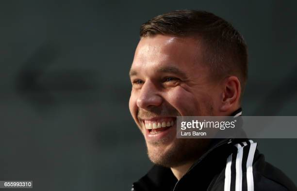 Lukas Podolski smiles during a press conference of the German national team ahead of the international friendly match against England at the Deutsche...