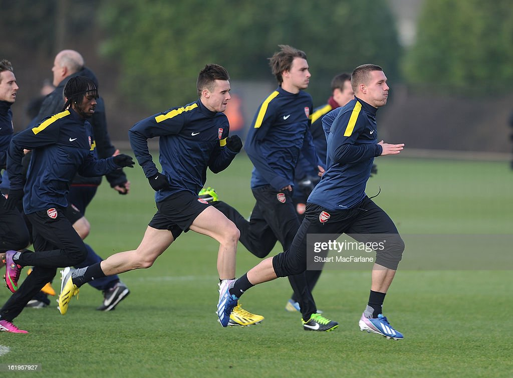 Lukas Podosli (R), Carl Jenkinson, Gervinho and Arsenal players sprint during a training session ahead of their UEFA Champions League match against FC Bayern Muenchen at London Colney on February 18, 2013 in St Albans, England.
