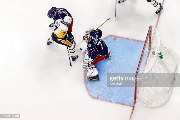 Lukas Sedlak of the Columbus Blue Jackets checks Matt Cullen of the Pittsburgh Penguins as Sergei Bobrovsky of the Columbus Blue Jackets makes a save...