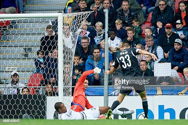 Lukas Spalvis of AaB Aalborg scores the 21 goal against Goalkeeper Stephan Andersen of FC Copenhagen during the Danish Alka Superliga match between...