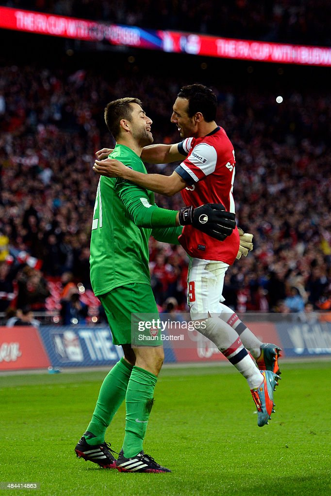 <a gi-track='captionPersonalityLinkClicked' href=/galleries/search?phrase=Lukasz+Fabianski&family=editorial&specificpeople=560874 ng-click='$event.stopPropagation()'>Lukasz Fabianski</a> of Arsenal and <a gi-track='captionPersonalityLinkClicked' href=/galleries/search?phrase=Santi+Cazorla&family=editorial&specificpeople=709830 ng-click='$event.stopPropagation()'>Santi Cazorla</a> of Arsenal celebrate victory during the FA Cup Semi-Final match between Wigan Athletic and Arsenal at Wembley Stadium on April 12, 2014 in London, England.