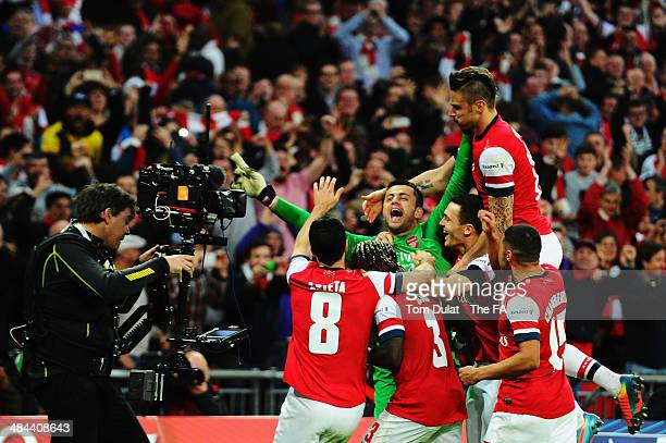 Lukasz Fabianski of Arsenal celebrates with teammates after winning the penalty shootout to claim victory in the FA Cup SemiFinal match between Wigan...