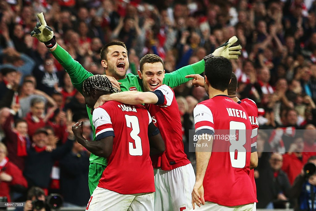 Lukasz Fabianski of Arsenal celebrates with team-mates after winning the penalty shoot-out to claim victory in the FA Cup Semi-Final match between Wigan Athletic and Arsenal at Wembley Stadium on April 12, 2014 in London, England.