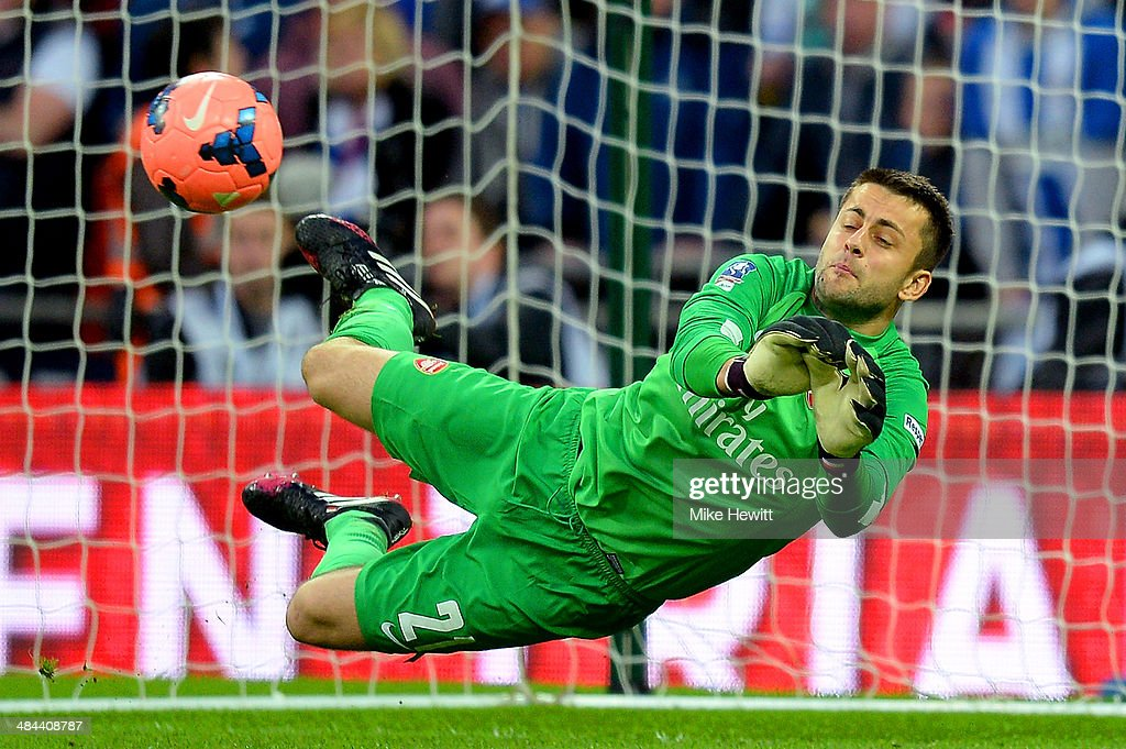 Lukasz Fabianski of Arsenal saves a penalty during the shootout during the FA Cup Semi-Final match between Wigan Athletic and Arsenal at Wembley Stadium on April 12, 2014 in London, England.