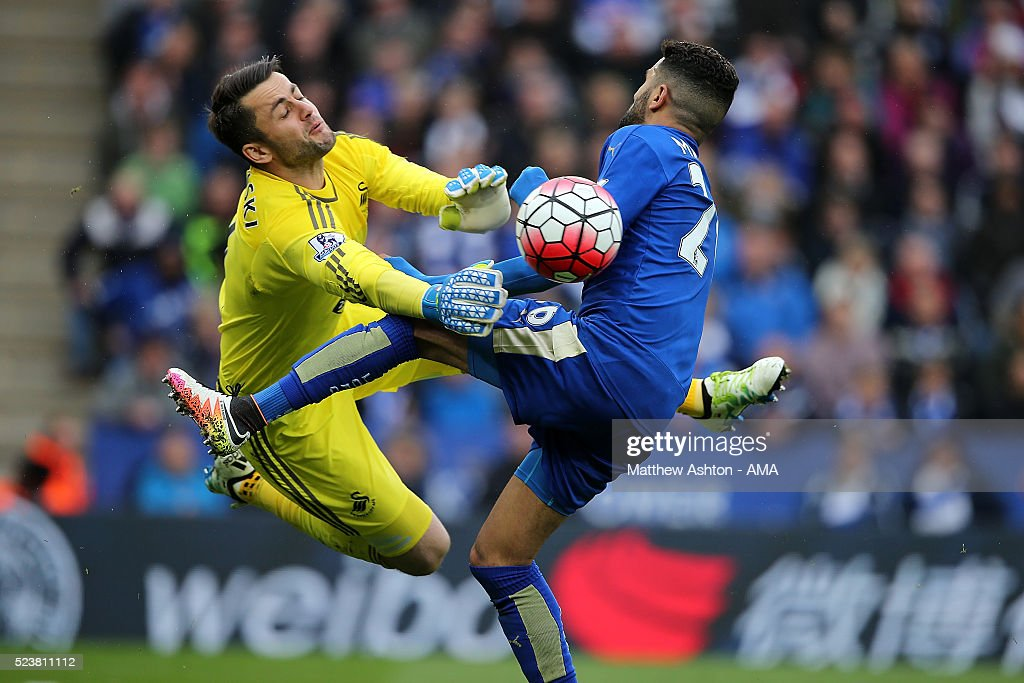 Lukasz Fabianski of Swansea City collides with Riyad Mahrez of Leicester City during the Barclays Premier League match between Leicester City and Swansea City at The King Power Stadium on April 24, 2016 in Leicester, United Kingdom.