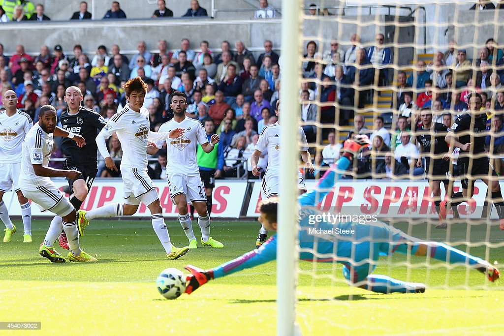 Lukasz Fabianski of Swansea City saves a shot from David Jones of Burnley during the Barclays Premier League match between Swansea City and Burnley at the Liberty Stadium on August 23, 2014 in Swansea, Wales.