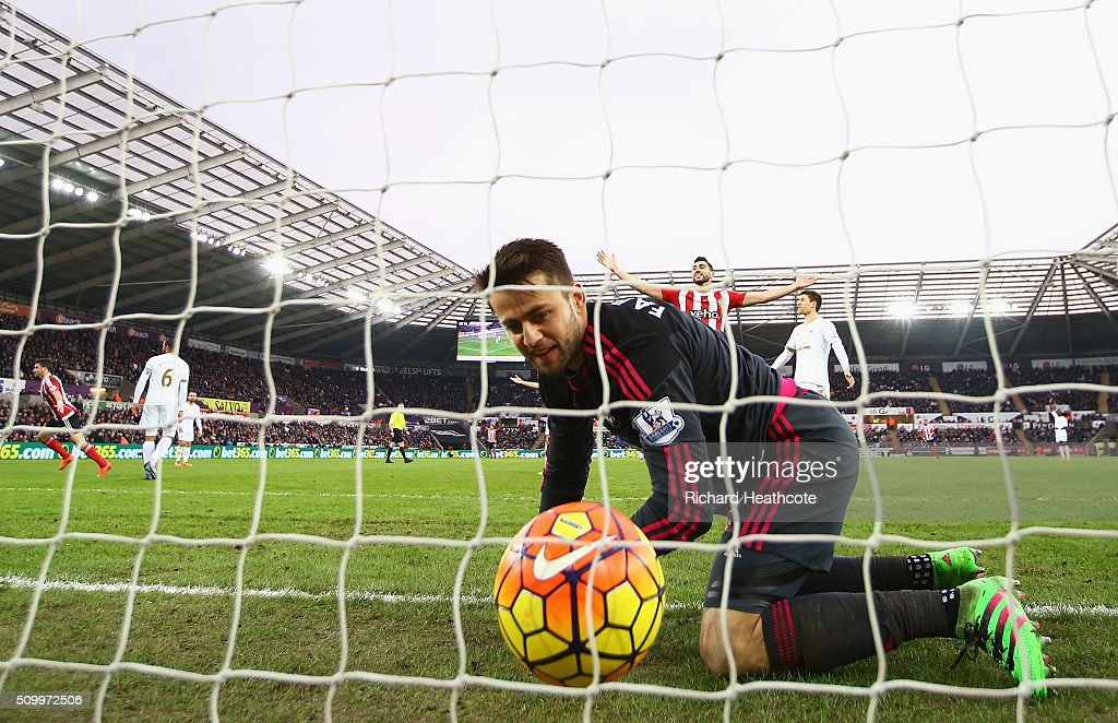 Lukasz Fabianski of Swansea City watches the ball at the back of the net after Shane Long (1st L) of Southampton scores his team's first goal during the Barclays Premier League match between Swansea City and Southampton at Liberty Stadium on February 13, 2016 in Swansea, Wales.