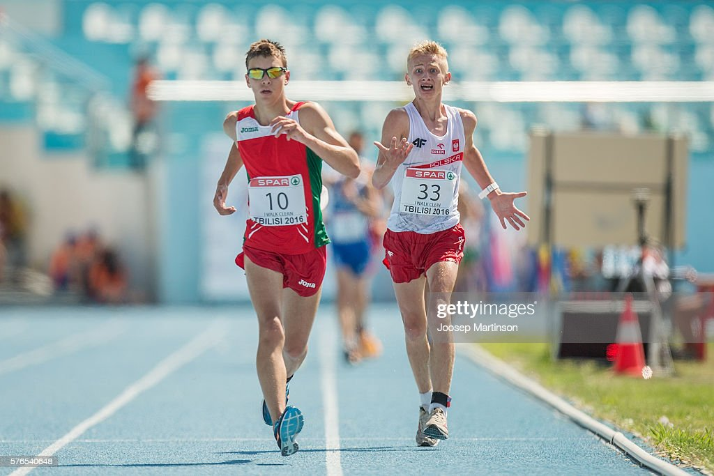 Lukasz Niedzialek of Poland protests against Mikita Kaliada of Belarus who was later disqualified for running in the Boys 10000m Race Walk during...