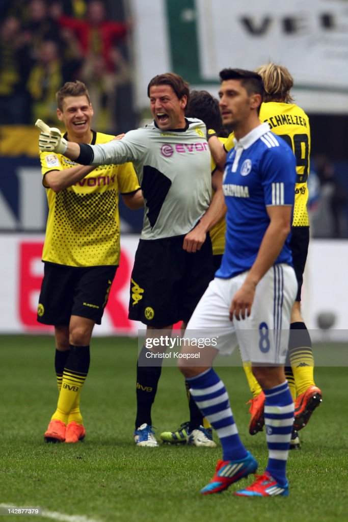 <a gi-track='captionPersonalityLinkClicked' href=/galleries/search?phrase=Lukasz+Piszczek&family=editorial&specificpeople=4380352 ng-click='$event.stopPropagation()'>Lukasz Piszczek</a> and <a gi-track='captionPersonalityLinkClicked' href=/galleries/search?phrase=Roman+Weidenfeller&family=editorial&specificpeople=726753 ng-click='$event.stopPropagation()'>Roman Weidenfeller</a> of Dortmund celebrate the 2-1 victory and <a gi-track='captionPersonalityLinkClicked' href=/galleries/search?phrase=Ciprian+Marica&family=editorial&specificpeople=2178476 ng-click='$event.stopPropagation()'>Ciprian Marica</a> of Schalke looks dejected after the Bundesliga match between FC Schalke 04 and Borussia Dortmund at Veltins Arena on April 14, 2012 in Gelsenkirchen, Germany.