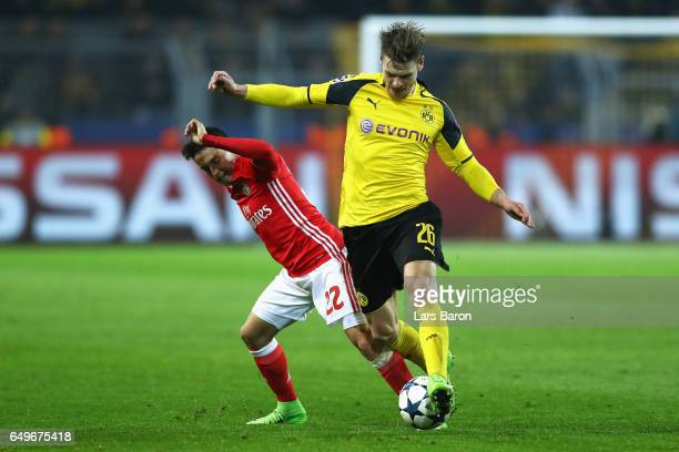 Lukasz Piszczek of Borussia Dortmund battles for the ball with Franco Cervi of SL Benfica during the UEFA Champions League Round of 16 second leg...