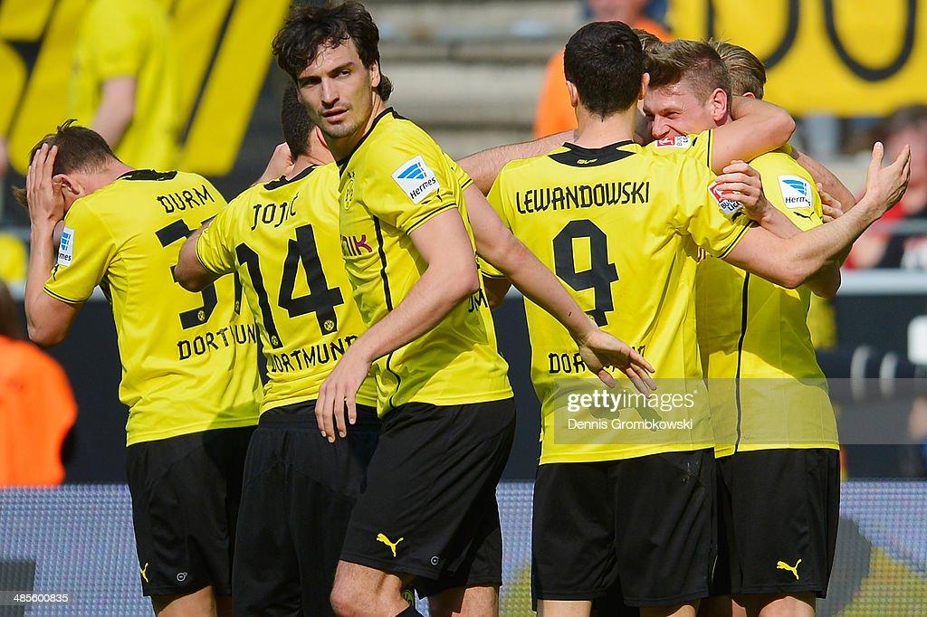 Lukasz Piszczek of Borussia Dortmund celebrates with team mates after scoring his team's third goal during the Bundesliga match between Borussia...