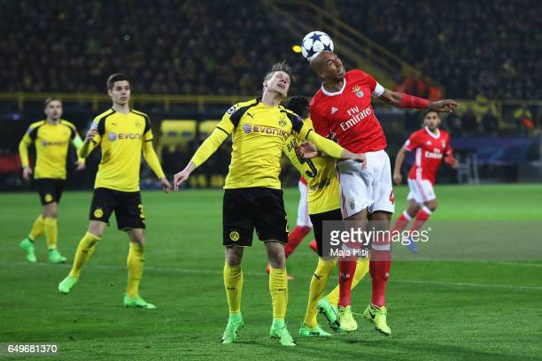 Lukasz Piszczek of Borussia Dortmund challenges for the headed ball with Luisao of SL Benfica during the UEFA Champions League Round of 16 second leg...