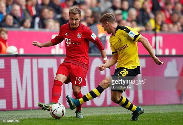 Lukasz Piszczek of Borussia Dortmund challenges Mario Goetze of Bayern Muenchen during the Bundesliga match between FC Bayern Muenchen and Borussia...