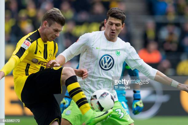 Lukasz Piszczek of Dortmund and Mario Gomez of Wolfsburg battle for the ball during the Bundesliga match between Borussia Dortmund and VfL Wolfsburg...
