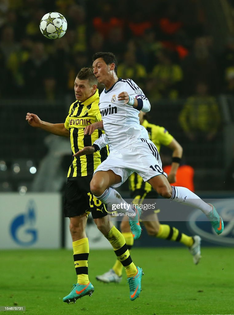 Lukasz Piszczek of Dortmund and Mesut Oezil of Madird head for the ball during the UEFA Champions League group D match between Borussia Dortmund and...