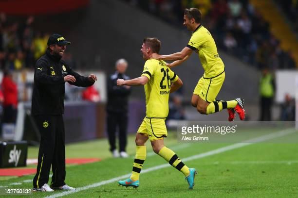 Lukasz Piszczek of Dortmund celebrates his team's first goal with head coach Juergen Klopp and team mate Moritz Leitner during the Bundesliga match...