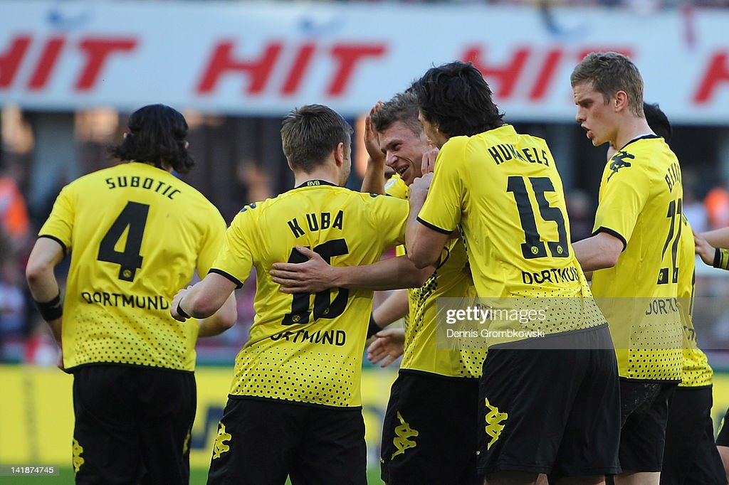 Lukasz Piszczek of Dortmund celebrates with teammates after scoring his team's first goal during the Bundesliga match between 1 FC Koeln and Borussia...