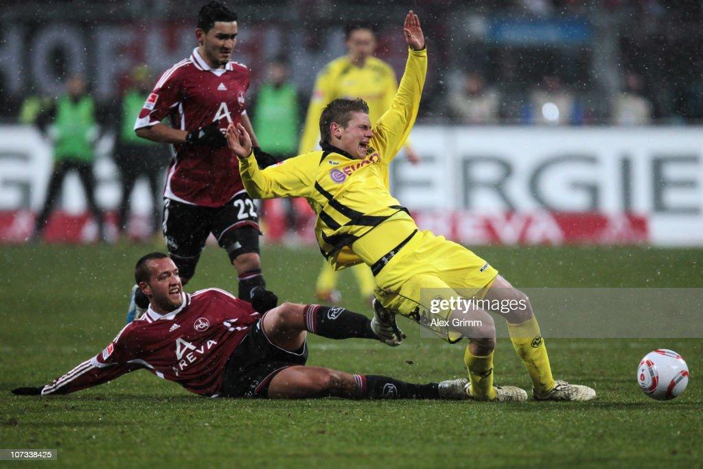 Lukasz Piszczek of Dortmund is challenged by Julian Schieber of Nuernberg during the Bundesliga match between 1 FC Nuernberg and Borussia Dortmund at...