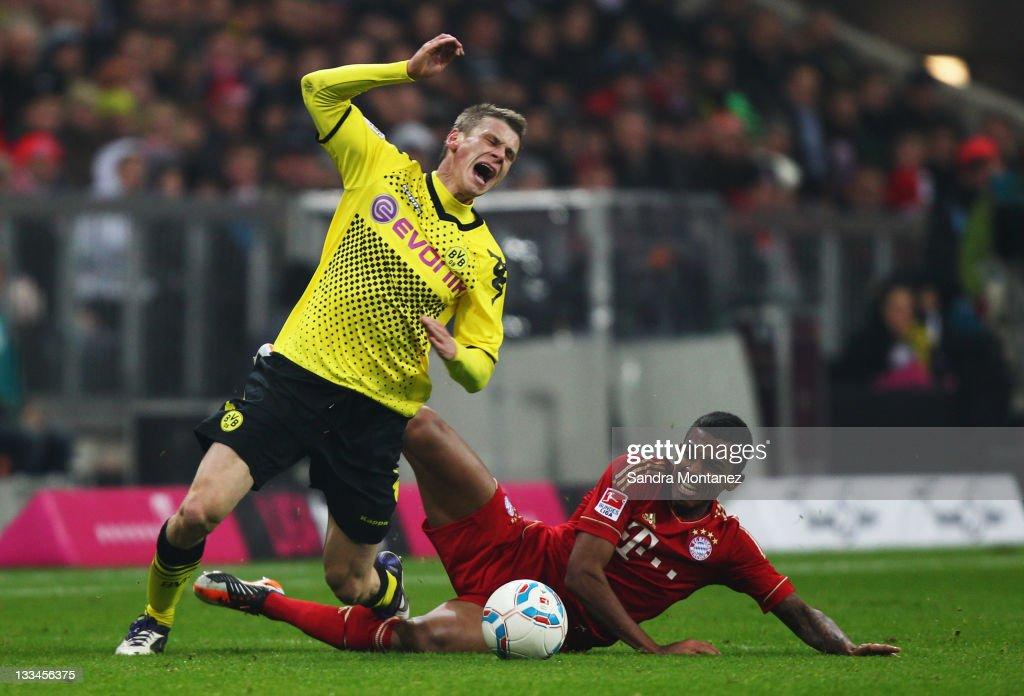 Lukasz Piszczek of Dortmund is tackled by Luiz Gustavo of Bayern during the Bundesliga match between FC Bayern Muenchen and Borussia Dortmund at...
