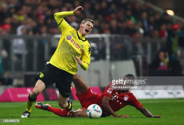 Lukasz Piszczek of Dortmund is tackled by Luiz Gustavo of Bayern during the Bundesliga match between FC Bayern Muenchen and Borussia Dortmund at...