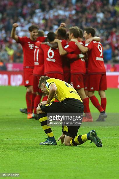 Lukasz Piszczek of Dortmund looks dejected whilst players of Muenchen celebrate the 5th team goal during the Bundesliga match between FC Bayern...