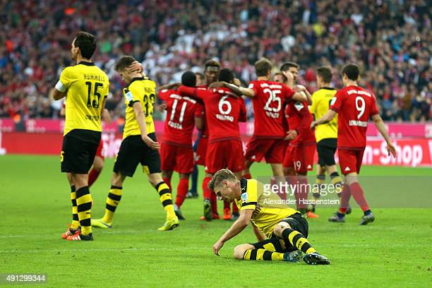Lukasz Piszczek of Dortmund looks dejected with his team mates Mats Hummels and Julian Weigl whilst players of Muenchen celebrate the 5th team goal...