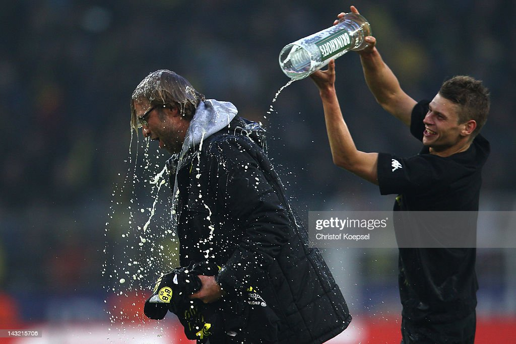 Lukasz Piszczek of Dortmund pours beer over head coach Juergen Klopp after winning 20 and the German Championships after the 1 Bundesliga match...