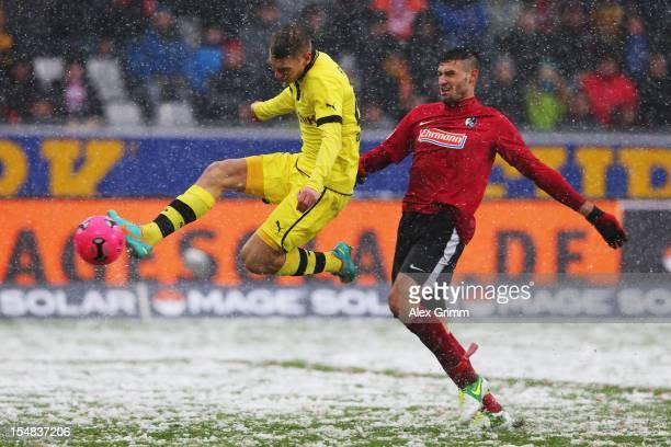 Lukasz Piszczek of Dortmund tries to score against Daniel Caligiuri of Freiburg during the Bundesliga match between SC Freiburg and Borussia Dortmund...