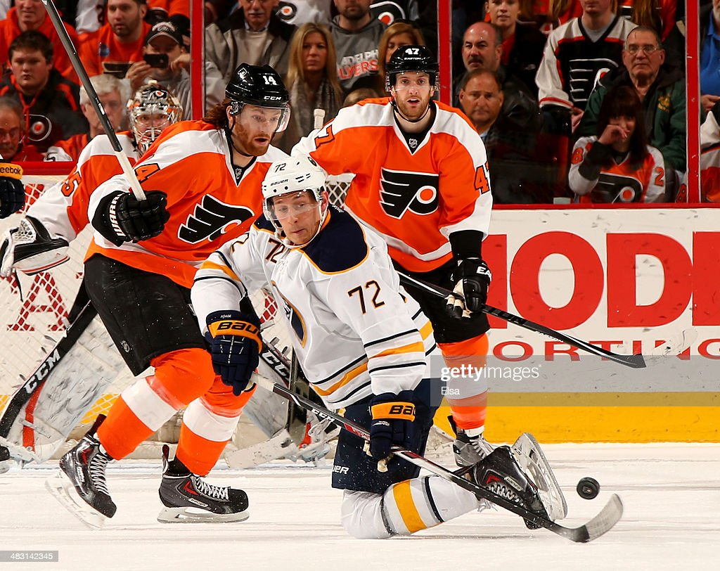 Luke Adam of the Buffalo Sabres and Sean Couturier of the Philadelphia Flyers fight for the puck in the second period at Wells Fargo Center on April...