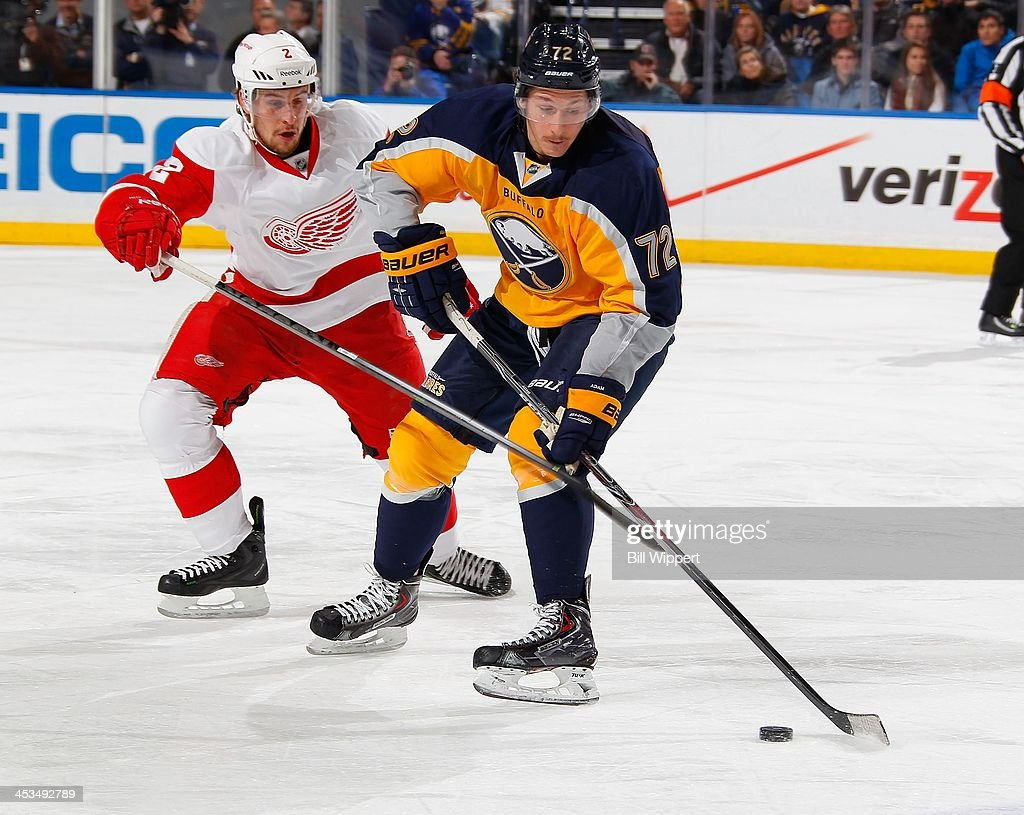 Luke Adam of the Buffalo Sabres controls the puck against Brendan Smth of the Detroit Red Wings on November 24 2013 at the First Niagara Center in...