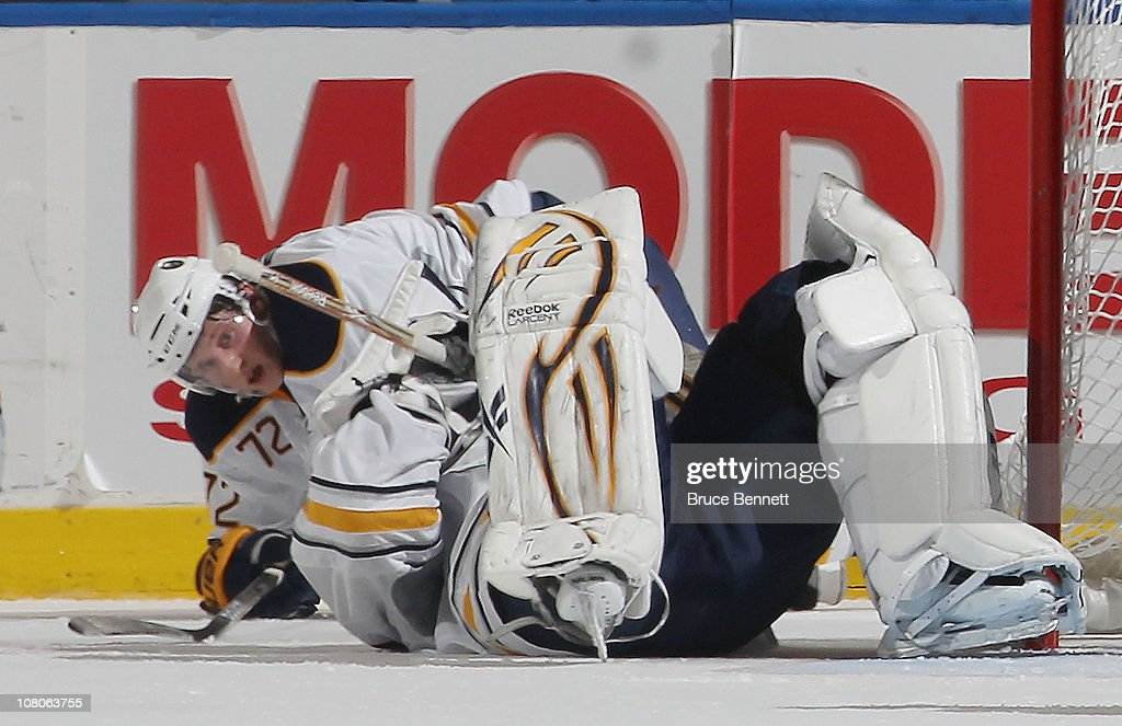 Luke Adam of the Buffalo Sabres looks back at Ryan Miller of the Buffalo Sabres after a collision in a game against the New York Islanders at the...