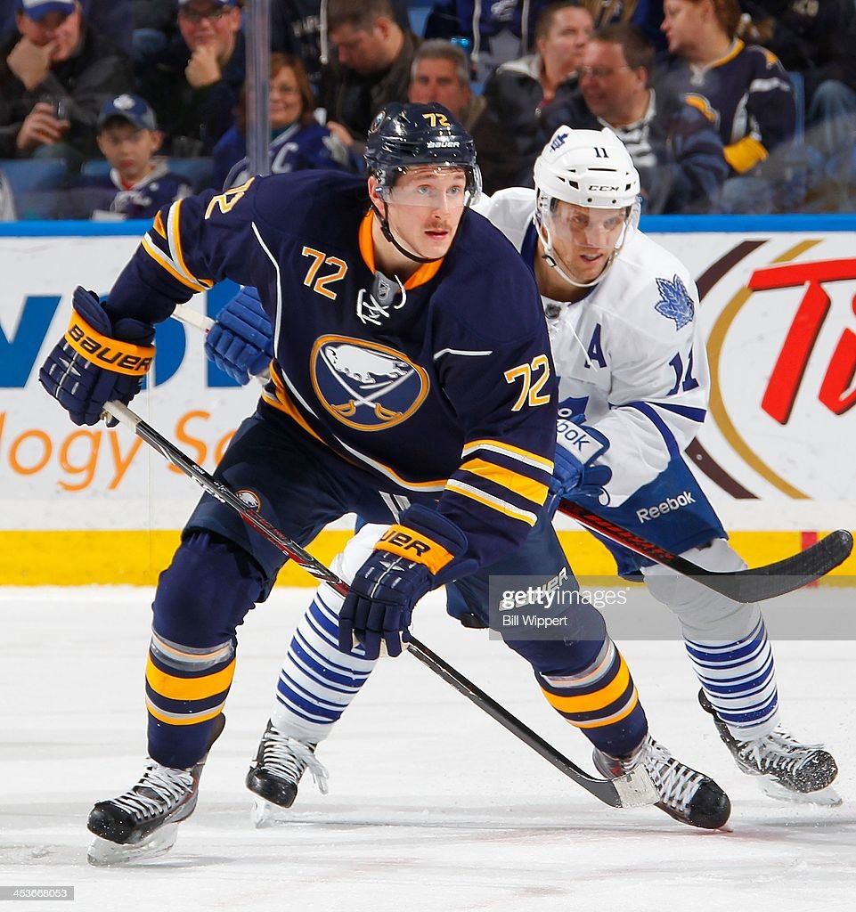 Luke Adam of the Buffalo Sabres skates against Jay McClement of the Toronto Maple Leafs on November 29 2013 at the First Niagara Center in Buffalo...