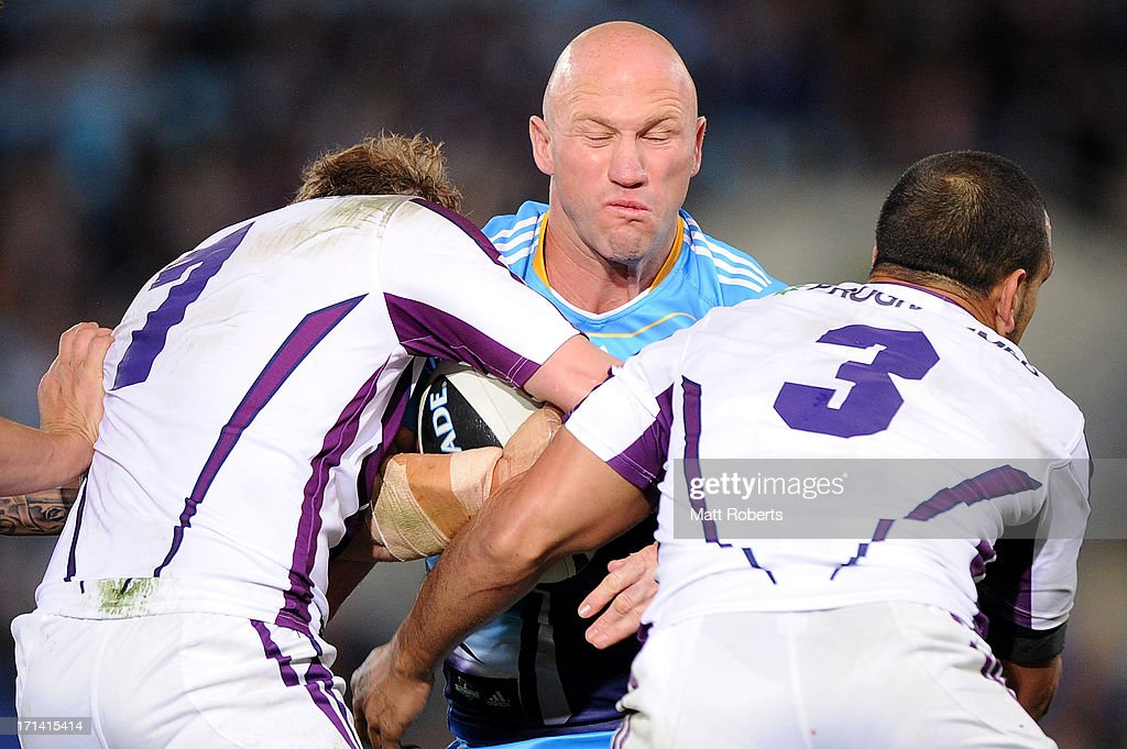<a gi-track='captionPersonalityLinkClicked' href=/galleries/search?phrase=Luke+Bailey&family=editorial&specificpeople=198882 ng-click='$event.stopPropagation()'>Luke Bailey</a> of the Titans is tackled during the round 15 NRL match between the Gold Coast Titans and the Melbourne Storm at Skilled Park on June 24, 2013 on the Gold Coast, Australia.