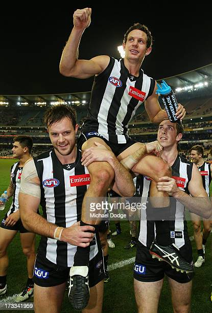 Luke Ball of the Magpies gets carried off after his 200th game by Nathan Brown and Nick Maxwell during the round 16 AFL match between the Collingwood...