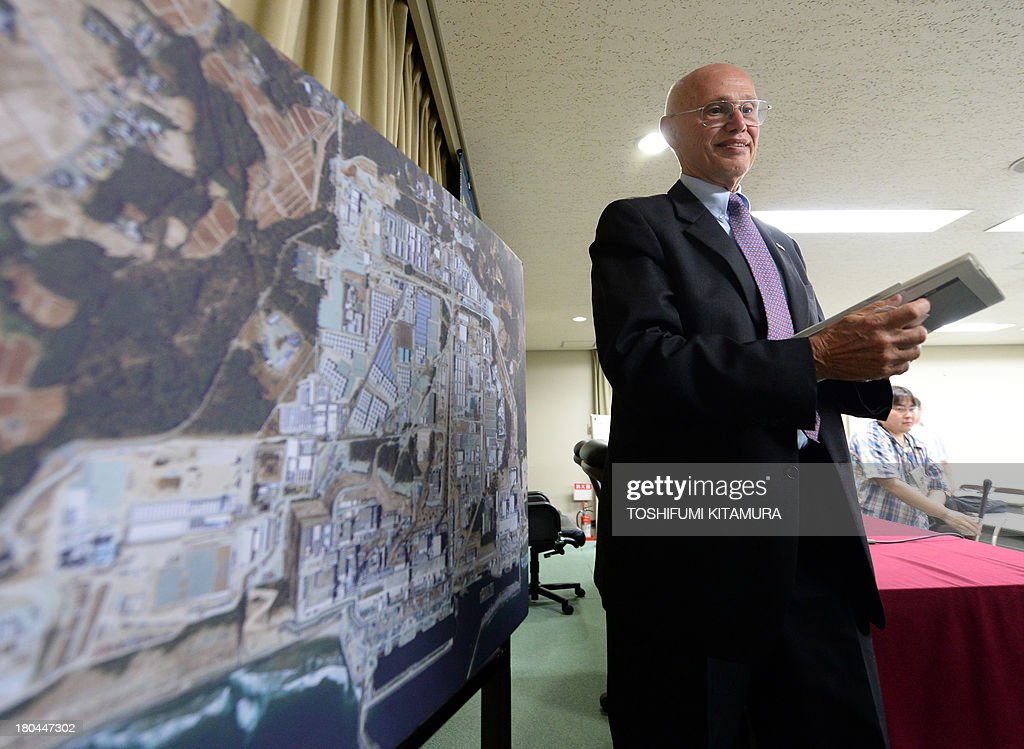 Luke Barret, external professional for Tokyo Electric Power's contaminated water and tank countermeasures headquarters, walks beside a picture of Fukushima Daiichi nuclear power plant after finishing his press conference in Tokyo on September 13, 2013. Thousands of tonnes of radioactive water are being stored in temporary tanks at the Fukushima Daiichi plant and TEPCO and Japanese officials are considering releasing some of it into the Pacific Ocean after filtering out radioactive materials, but face opposition from fisherman and neighbouring countries.