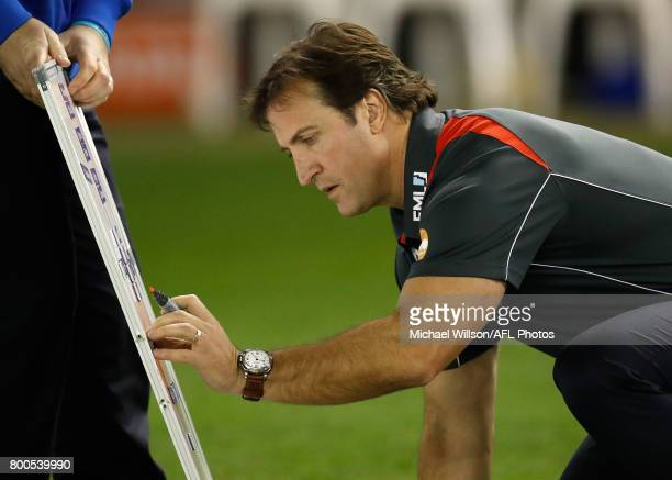 Luke Beveridge Senior Coach of the Bulldogs writes on a whiteboard during the 2017 AFL round 14 match between the Western Bulldogs and the North...
