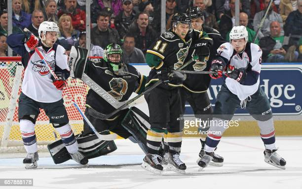 Luke Boka of the Windsor Spitfires tips a puck against Owen MacDonald of the London Knights during Game One of the OHL Western Conference Quarter...