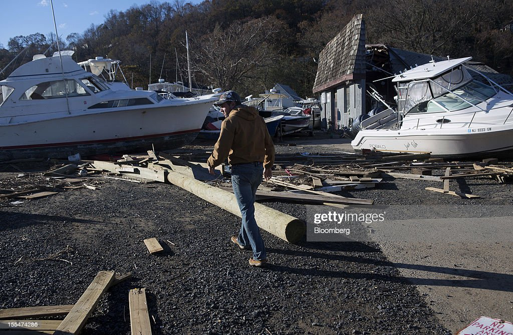"Luke Bollerman walks through damage from Hurricane Sandy in the marina and trailer park his family own in Highlands, New Jersey, U.S. on Saturday, Nov. 3, 2012. Recovery progressed slowly in New Jersey, where Hurricane Sandy struck on Oct. 29. New Jersey Governor Chris Christie, a Republican, praised the ""patience and resilience"" of New Jerseyans and released a timeline Saturday of which neighborhoods without electricity should be restored over the next few days. Photograph: Victor J. Blue/Bloomberg via Getty Images"