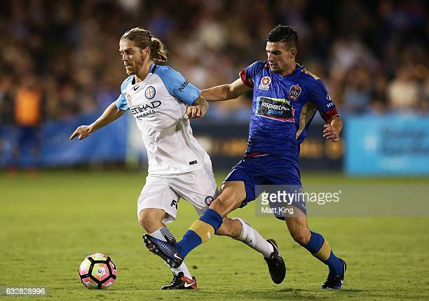 Luke Brattan of Melbourne City is challenged by Steven Ugarkovic of the Jets during the round 17 ALeague match between the Newcastle Jets and...