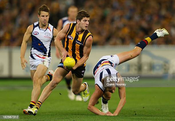Luke Breust of the Hawks avoids a tackle by Bernie Vince of the Crows during the second AFL Preliminary Final match between the Hawthorn Hawks and...