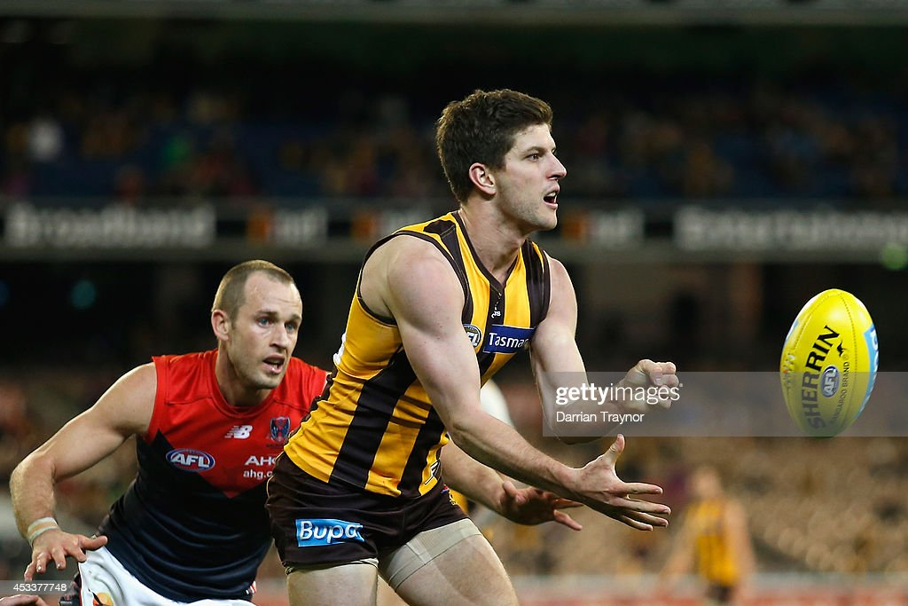 Luke Breust of the Hawks handballs in front of Daniel Cross of the Demons during the round 20 AFL match between the Hawthorn Hawks and the Melbourne Demons at Melbourne Cricket Ground on August 9, 2014 in Melbourne, Australia.